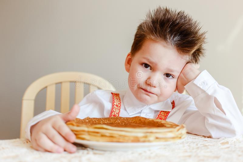 Maslenitsa russe le garçon s'assied à une table avec un plat des crêpes frites Crêpes le Mardi gras image libre de droits