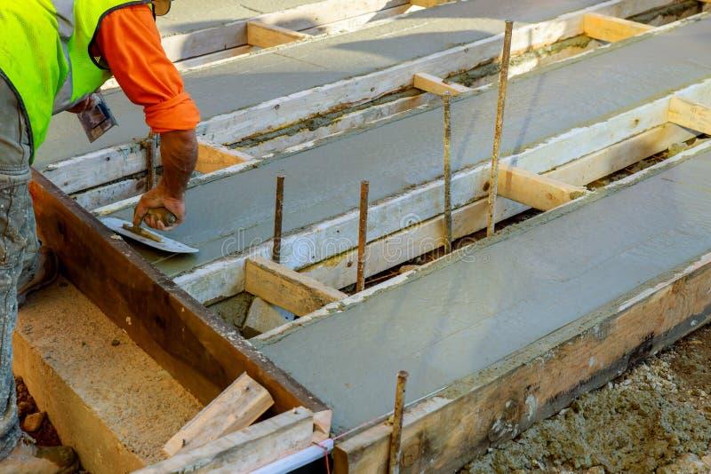 Mason που χτίζει ένα τσιμέντο παλτών κατεβατών στην εργασία πατωμάτων χύνοντας συγκεκριμένο πεζοδρόμιο στοκ φωτογραφίες