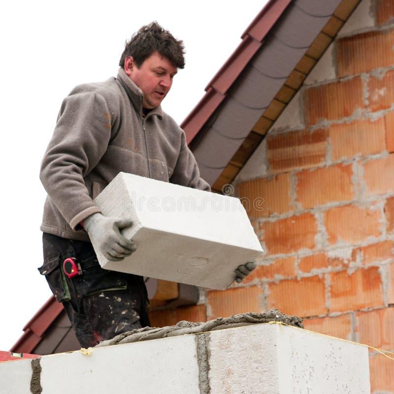 Mason. Building new wall with white bricks royalty free stock photography