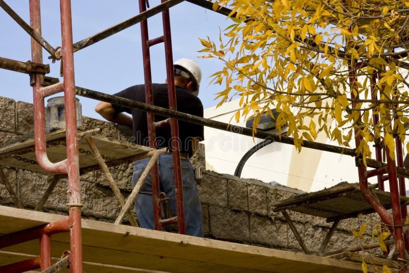 Mason brick layer. On a scafold building a wall stock photos