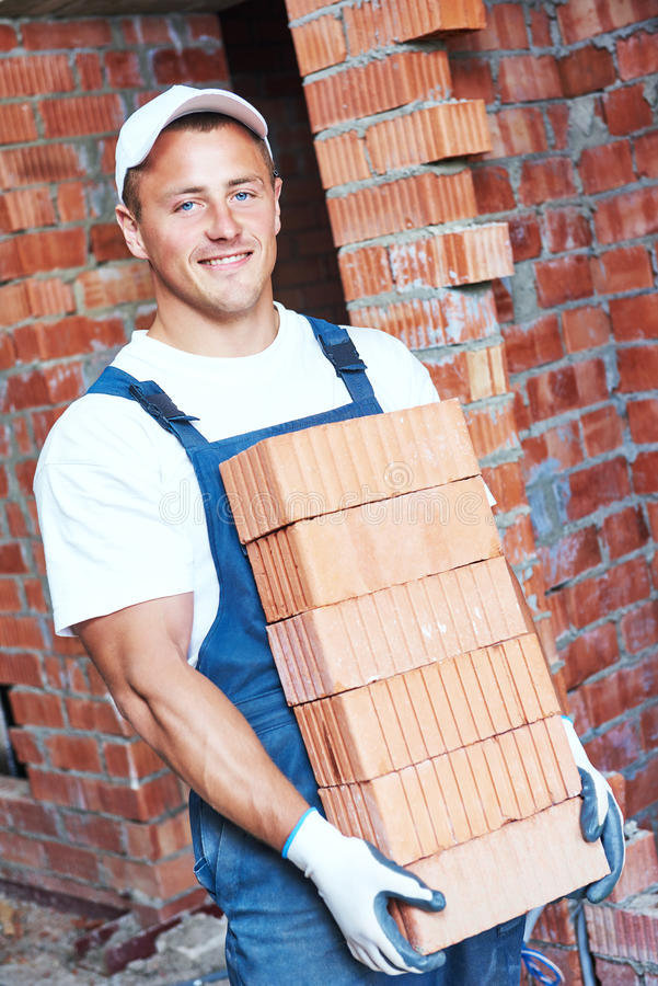 Mason bricklayer carrying red bricks stock photography
