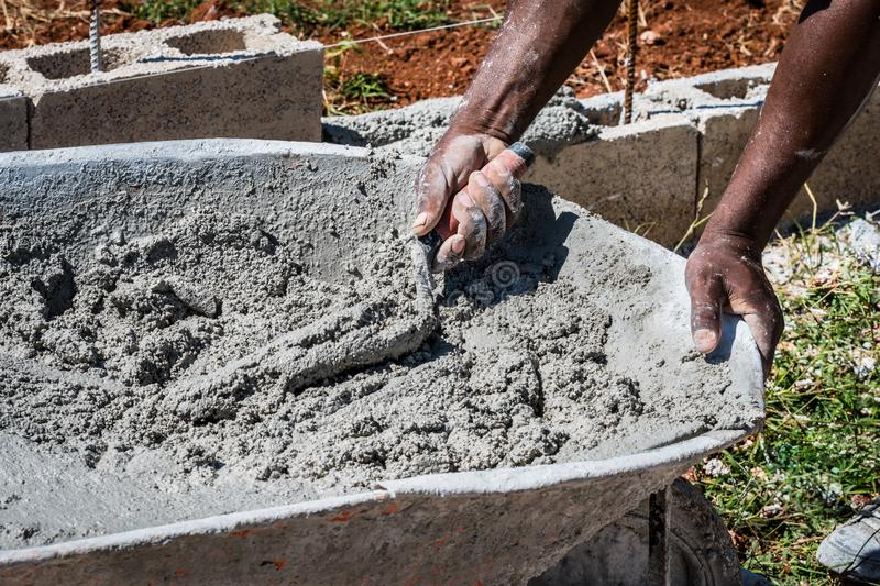 Mason/bricklayer/construction worker scooping wet cement from wheel barrow stock photos