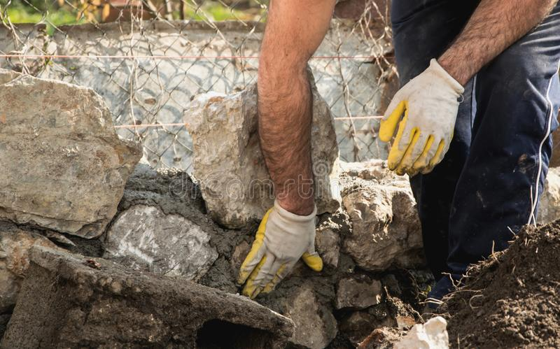Mason building a stone wall, authentic working person. Mason building a stone wall, construction industry concept royalty free stock photography