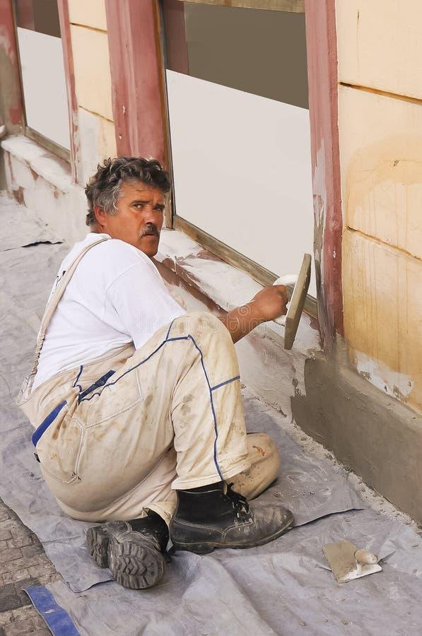 Mason doing some construction repairs stock photos
