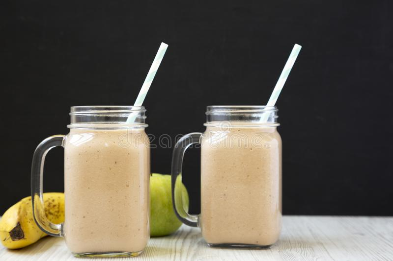 Mason glass jar mugs filled with banana apple smoothie, side view. Closeup royalty free stock photography