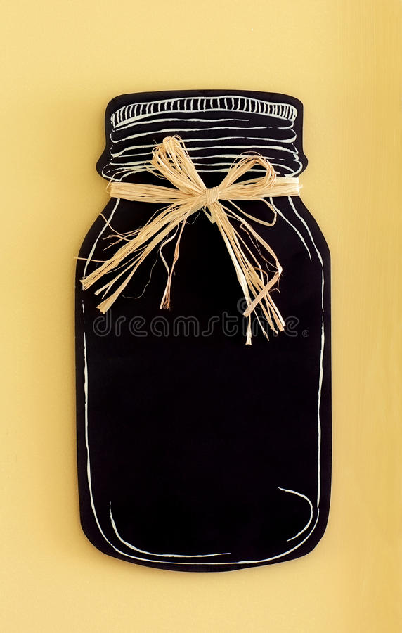 Mason Jar Chalkboard With Raffia Tie On Rustic Yellow Background In Vertical Format
