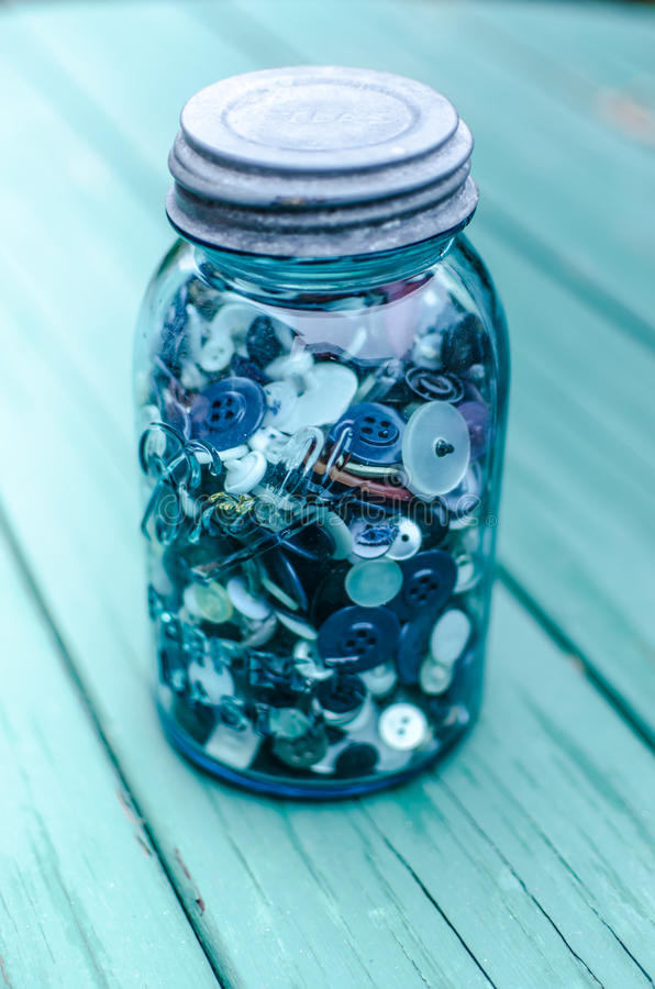 Mason Jar Filled with buttons. A blue ball mason jar with steel top filled with assorted buttons on a picnic table royalty free stock photography