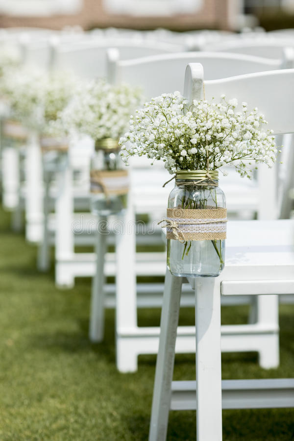 Mason jar and flowers at wedding. Mason jar with flowers hanging from chair at wedding stock photography