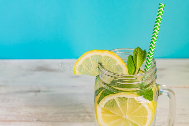 Mason jar glass of homemade lemonade with lemons, mint and paper straw on turquoise background. Summer refreshing beverage royalty free stock image