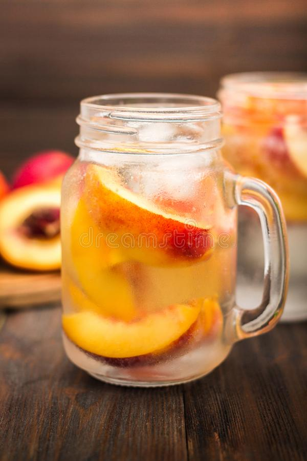 Download Mason Jar Glass Of Homemade Peach Iced Water On A Rustic Wooden Background Stock