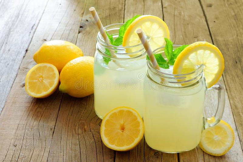 Mason jar glasses of homemade lemonade on rustic wood. Two mason jar glasses of homemade lemonade on a rustic wooden background royalty free stock images