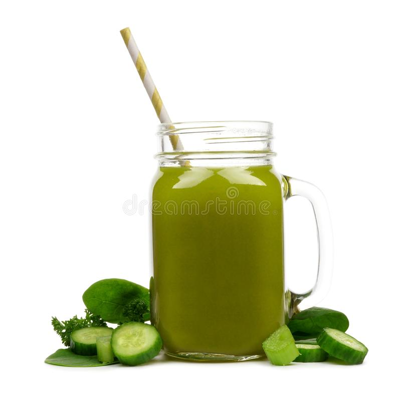 Mason jar of green vegetable juice with surrounding ingredients, isolated royalty free stock image