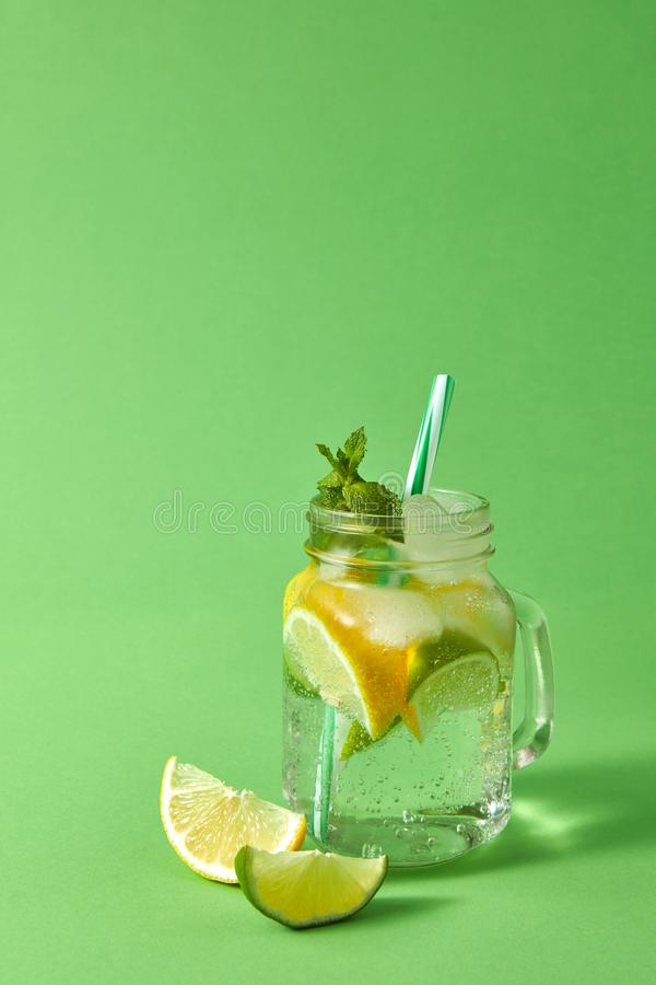 Mason jar with homemade sparkling lemonade with ice, slices of lime and lemon, leaf of mint with plastic straws on a. Glass jar on a green table with homemade stock photography