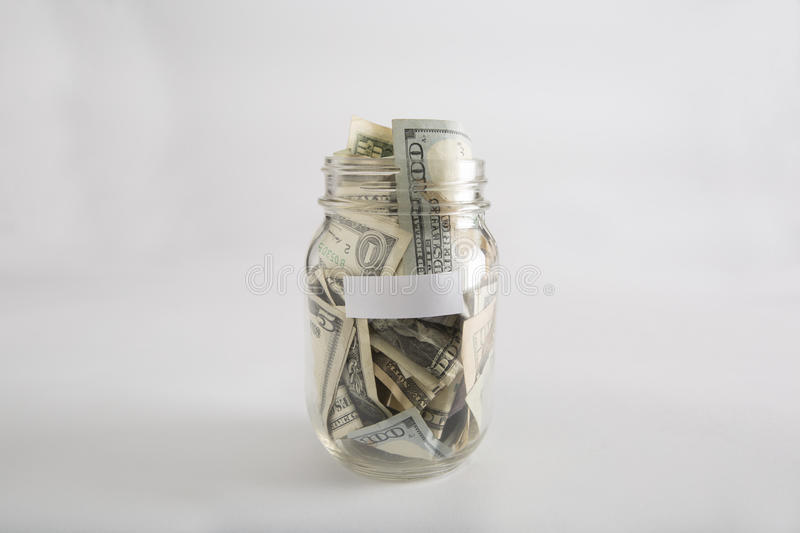 Mason jar with money with blank label royalty free stock photo