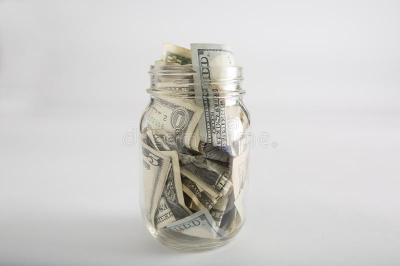 Mason jar with money and different dollar amounts stock photography