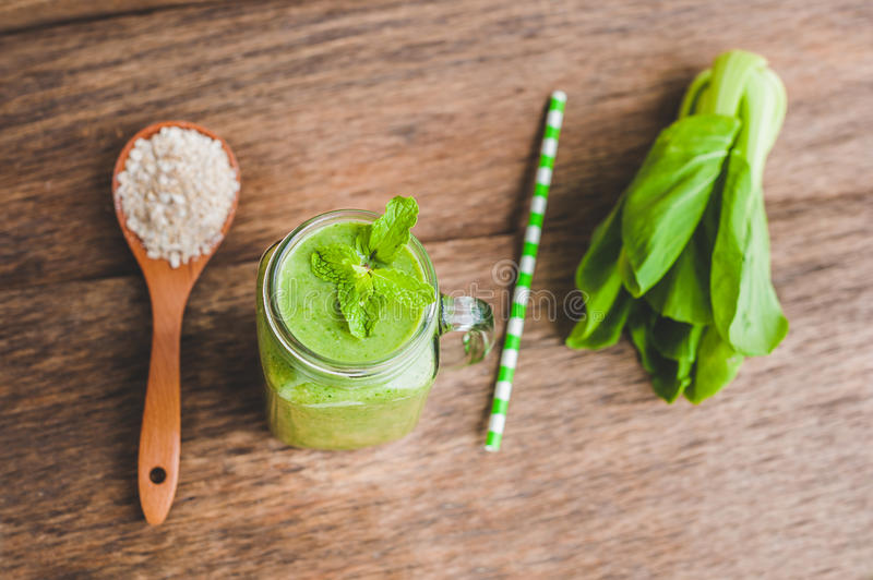 Mason jar mugs filled with green spinach, banana and coconut milk health smoothie with with a spoon of oatmeal on wooden rustic ta royalty free stock image