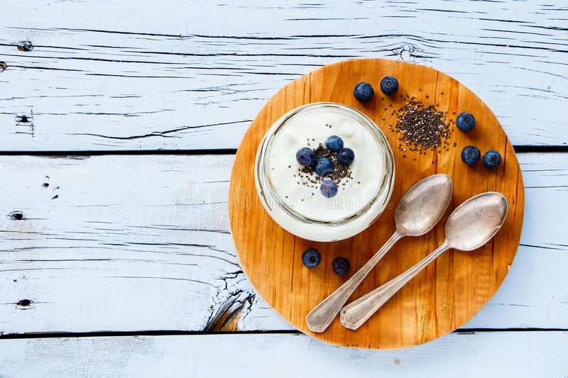 Mason jar of yogurt. Mason jar of diet yogurt with chia seeds and fresh blueberries for healthy breakfast on white grunge wooden background, top view, copy space stock images