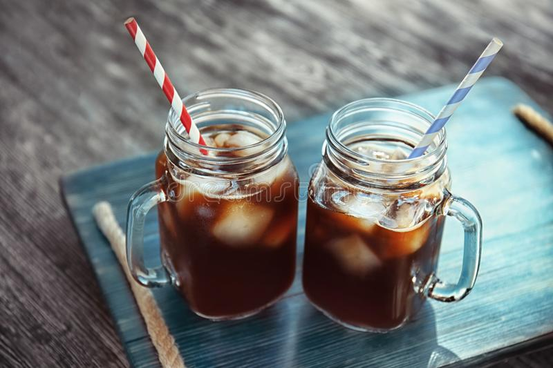 Mason jars with cold brew coffee. On wooden tray royalty free stock photography