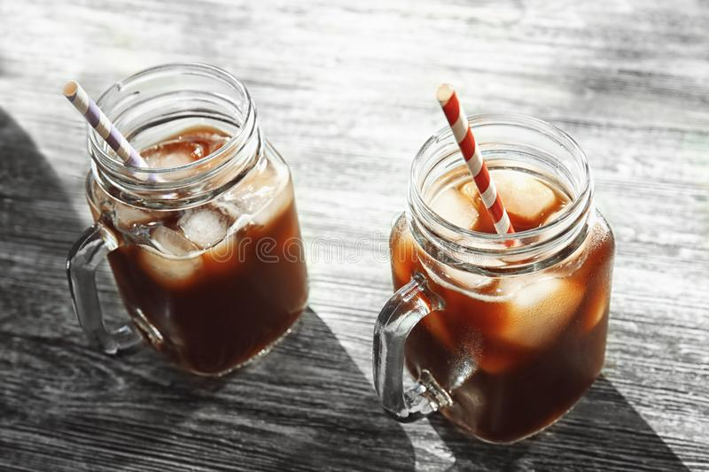 Mason jars with cold brew coffee and straws. On wooden table stock photos