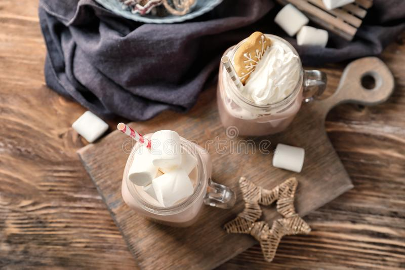 Mason jars of hot cocoa drink on wooden board royalty free stock image