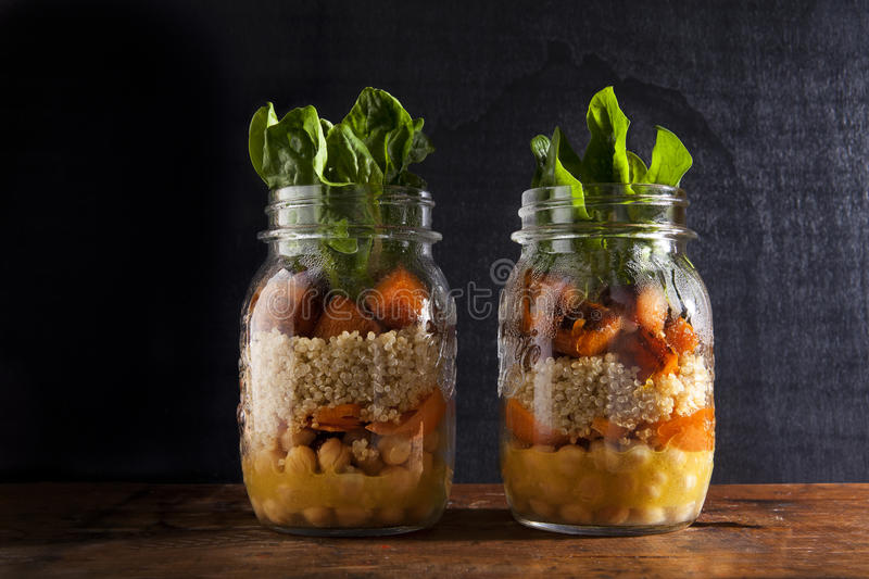 Mason jars with hot Salad: Chickpeas, arrots, quinoa, roasted Pu stock image