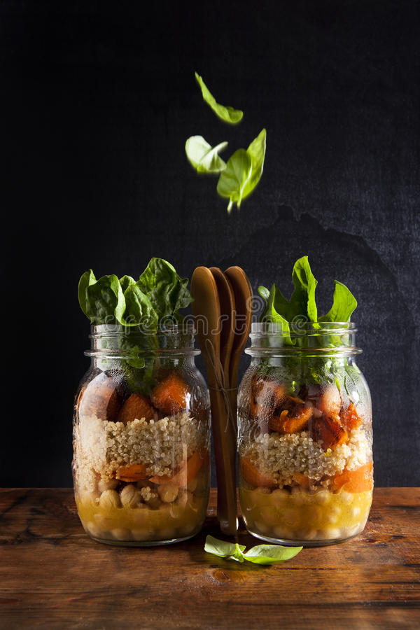 Mason jars with hot Salad: Chickpeas, arrots, quinoa, roasted Pu royalty free stock photos