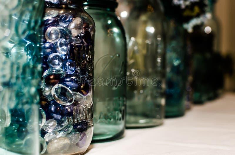 Mason Jars lined up. Blue, aqua and green mason jars in a line royalty free stock image