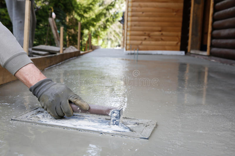 Mason leveling and screeding concrete floor base stock image image mason leveling and screeding concrete floor base with square trowel in front of the house construction business do it yourself precision work around the solutioingenieria Choice Image