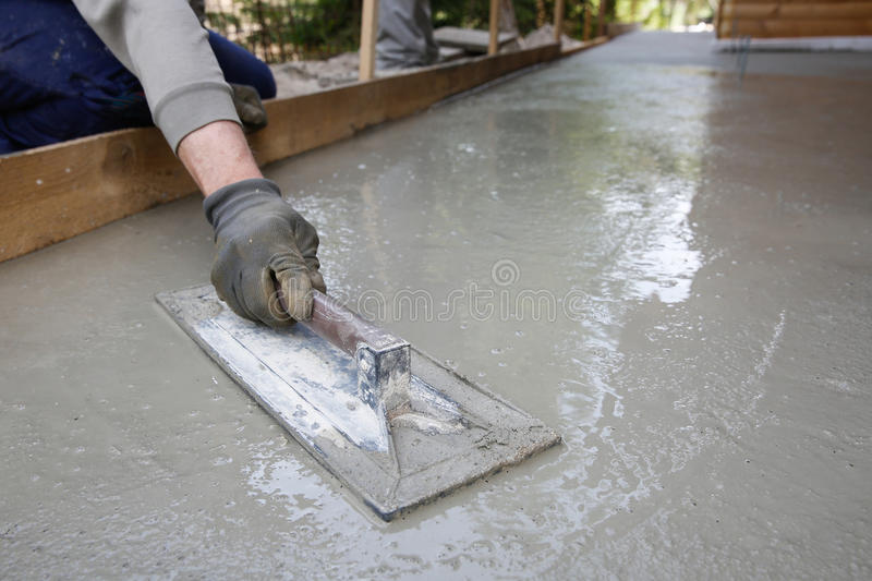Mason leveling and screeding concrete floor base stock photo image mason leveling and screeding concrete floor base with square trowel in front of the house construction business do it yourself precision work around the solutioingenieria Choice Image