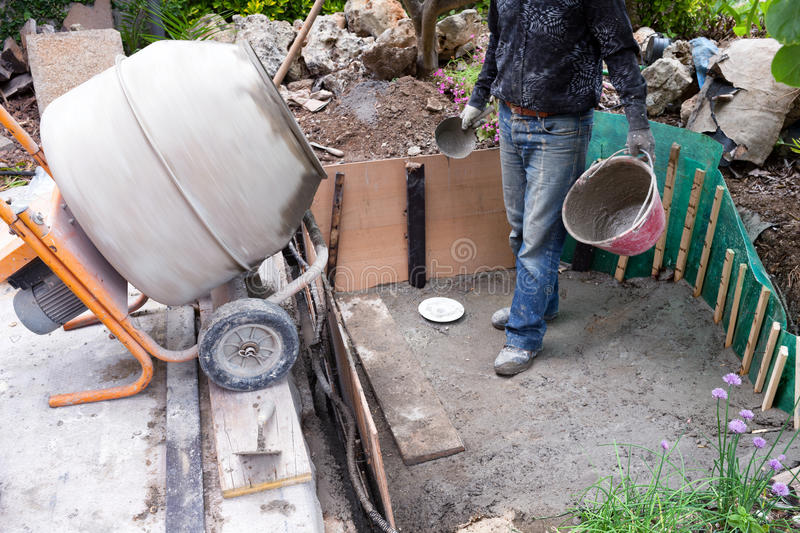 Mason Making Small Pond In The Garden. Mason waiting for the fresh cement to be prepared by the cement mixer, during the building of artificial pond in the royalty free stock images