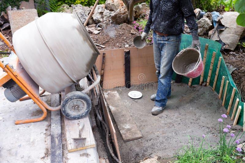 Mason Making Small Pond In le jardin images libres de droits