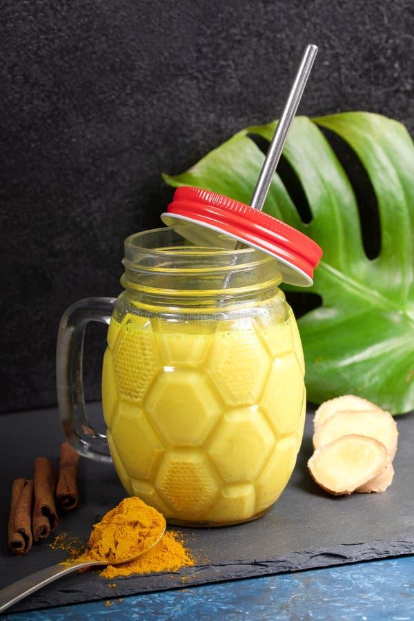 Mason-pot van gouden turmere melk met metaalstro, ingrediënten voor het koken ervan, monstera-blad op zwart Verticale foto royalty-vrije stock afbeeldingen