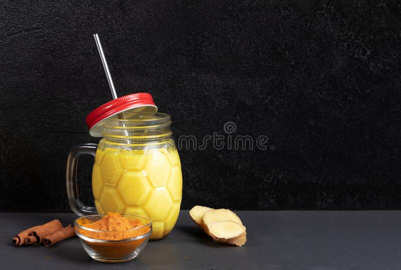 Mason-pot van gouden turmere melk met metaalstro, ingrediënten voor het koken op zwarte achtergrond Kopieerruimte stock afbeelding