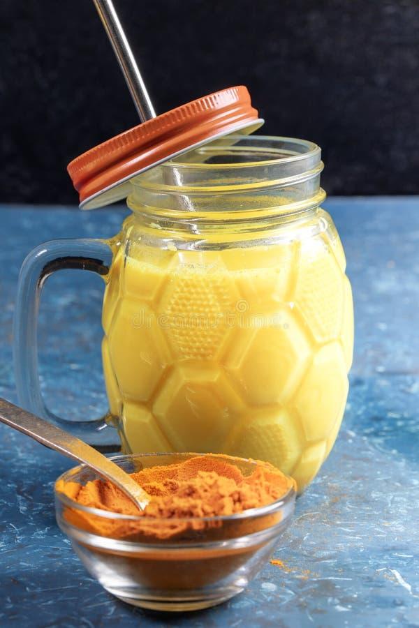 Mason-pot van gouden turmere melk met metaalstro, kurkuma-poeder voor het koken op blauw Verticale foto royalty-vrije stock fotografie