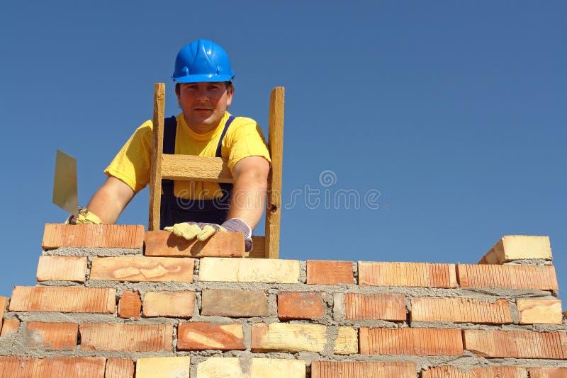 Mason at work. Mason building brick wall standing on wooden ladder stock image