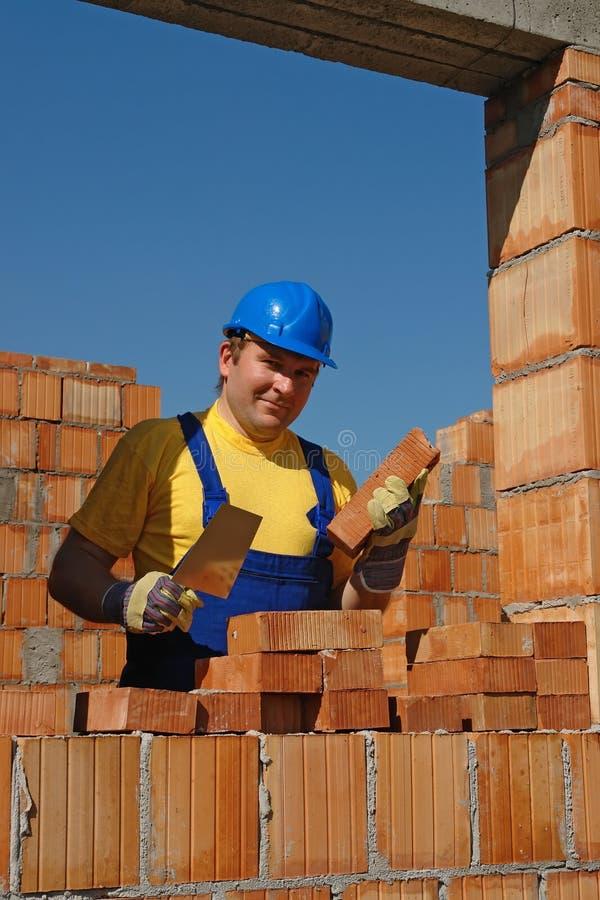 Mason at work. Mason in blue helmet building house wall in bricks stock photos