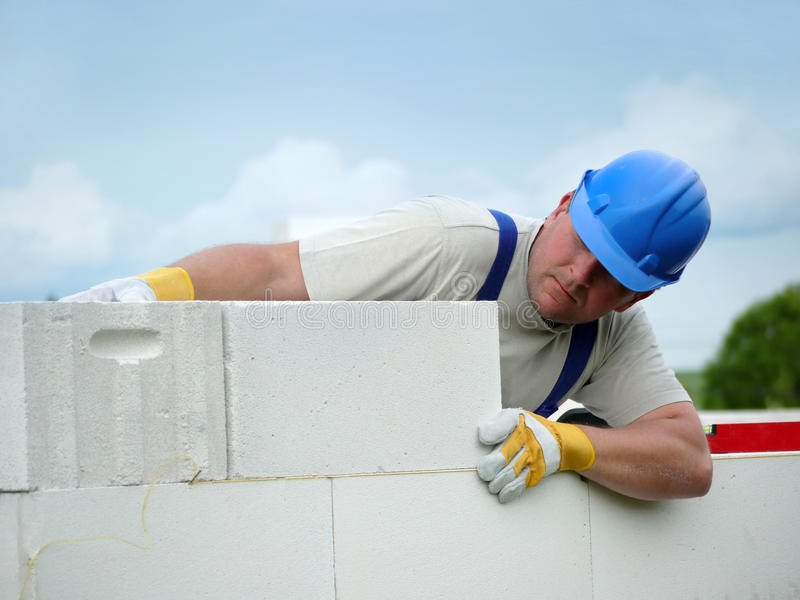 Mason at work. Mason aligning aerated autoclaved concrete block of constructed house wall royalty free stock images