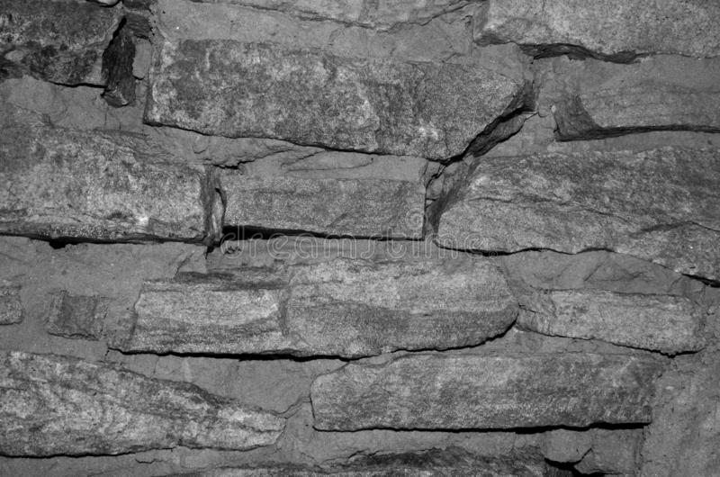 Masonry stone wall is covered with moisture in black and white. The graphic resource consists of wet masonry walls stock photos