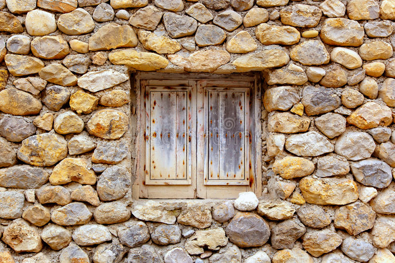 Masonry stone wall with grunge wood window. Balearic islands masonry stone wall with grunge wood window royalty free stock photos