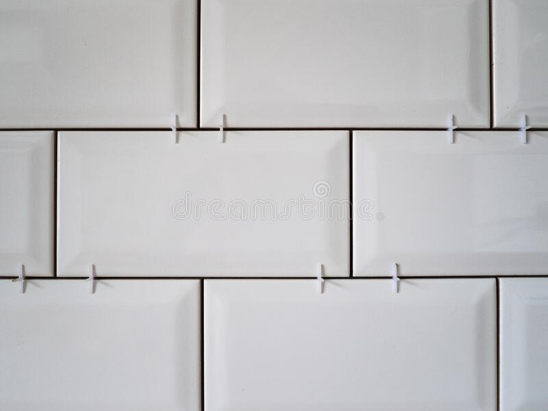 Masonry on the wall of white ceramic tiles. Bathroom or kitchen renovation royalty free stock photography