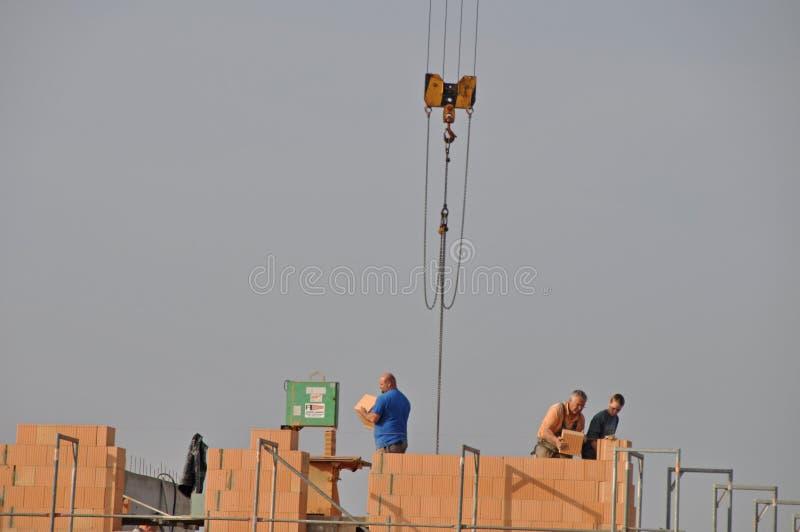 Masons laying bricks standing high on scaffolding royalty free stock photography