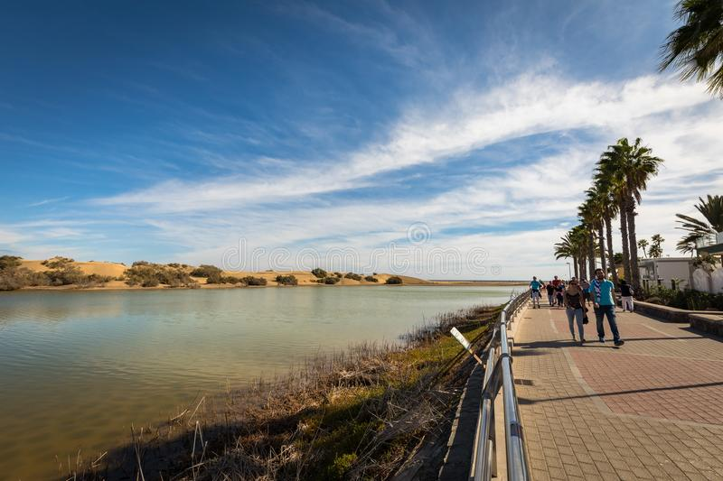 Maspalomas in Gran Canaria, Spain - December 11, 20017: La Charca, bird observation place in Maspalomas Dunes nature. Reserve. Promenade walk with tourists on stock images