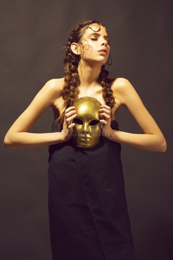 Masque d'or à disposition de belle femme mystérieuse, charme photo stock
