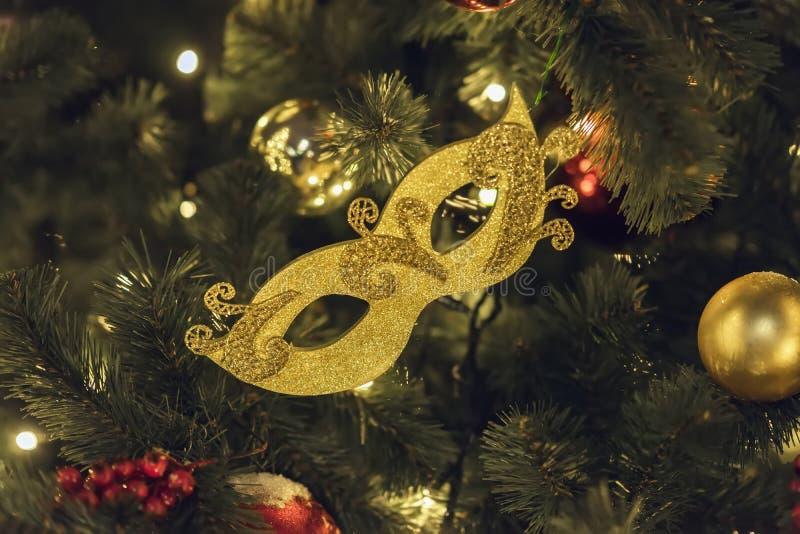 Masque d'or de carnaval et boules brillantes lumineuses de celluloïde sur l'arbre de Noël Occasions de fête concept, vacances, No photo stock