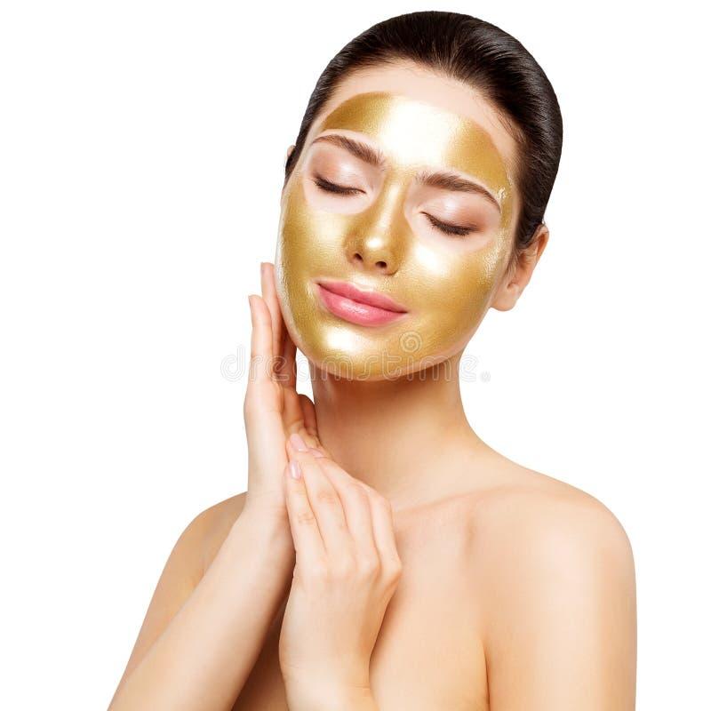 Masque d'or de femme, beau modèle avec le visage cosmétique de contact de peau d'or, soins de la peau de beauté et traitement photos libres de droits