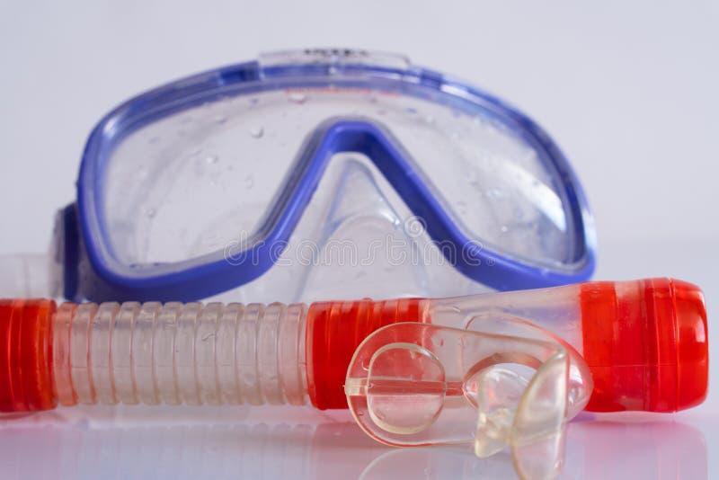 Masque de natation de silicone bleu sur la table blanche avec la réflexion photos libres de droits