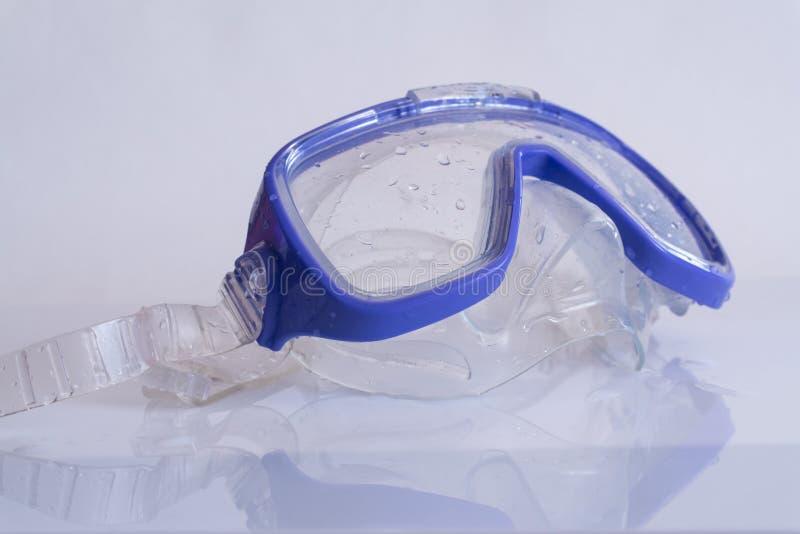 Masque de natation de silicone bleu sur la table blanche avec la réflexion images stock