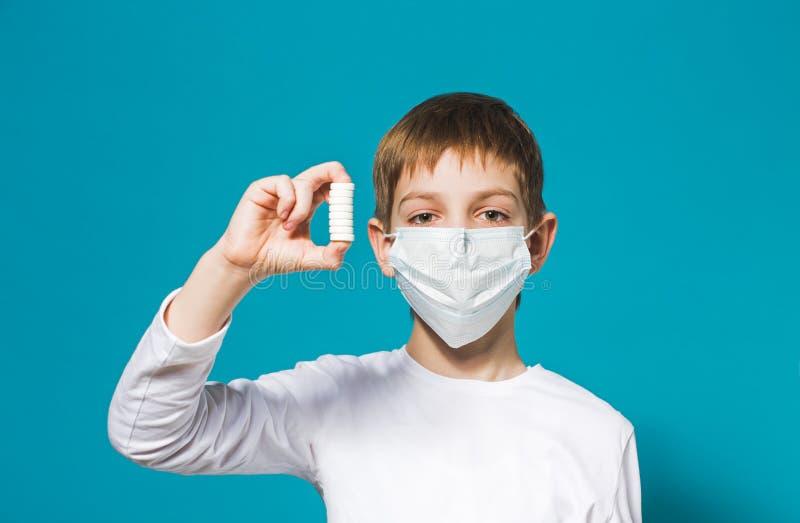 Masque de protection de garçon tenant des pilules photo stock