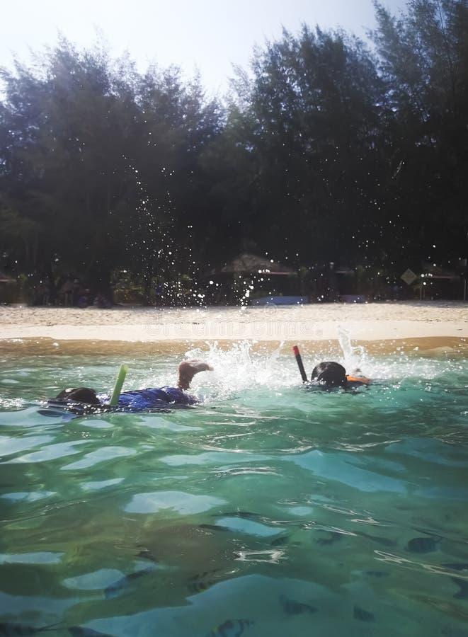 masque naviguant au schnorchel de personnes dans l'eau photographie stock
