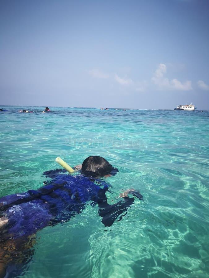 Masque naviguant au schnorchel de port d'enfant dans l'eau image libre de droits